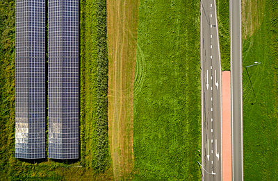 Solar panels and road among fields, Netherlands - p1132m2215542 by Mischa Keijser
