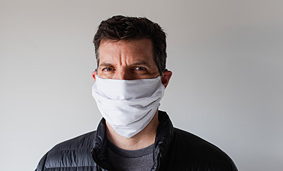 Man wearing homemade cloth face mask during Covid 19 pandemic. - p1166m2174103 by Cavan Images