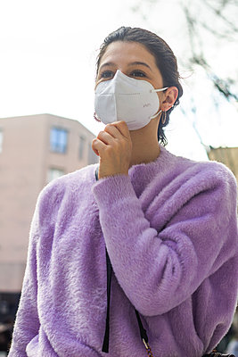 young woman with KN95 protective mask on the street - p1166m2258372 by Cavan Images