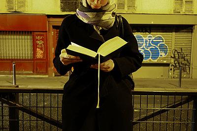 Junge Frau liest ein Buch auf der Straße - p1189m1218637 von Adnan Arnaout