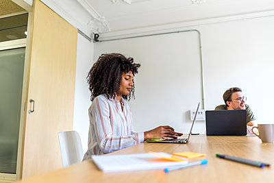 Young female entrepreneur with male colleague working on laptop while sitting in board room at office - p300m2264486 by VITTA GALLERY