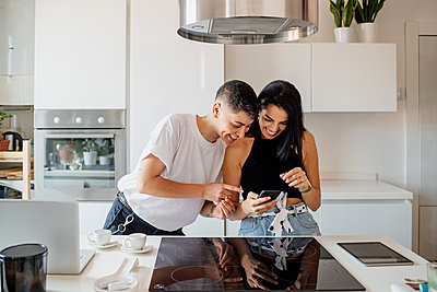 Young lesbian couple standing in kitchen, looking at mobile phone. - p429m2208587 by Eugenio Marongiu