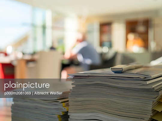 Stack of magazines in living room with man in background - p300m2081069 by Albrecht Weißer