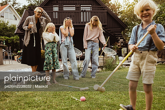 Boy with polo mallet standing by family in back yard at evening - p426m2238032 by Maskot