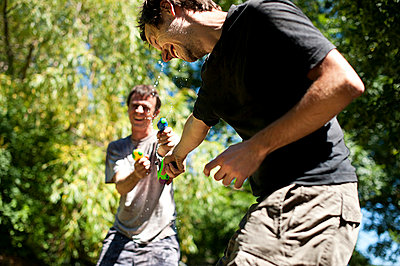 Two men playing with water guns 2 - p1007m854426 by Tilby Vattard