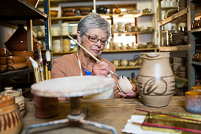 Female potter painting on bowl - p1315m1199623 by Wavebreak