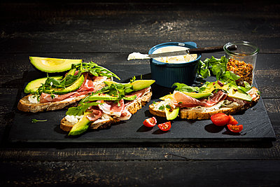 Onion bread with cream cheese, parma ham, avocado, rucola, thyme and tomato - p300m1587804 by Roman Märzinger