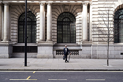 UK, London, stylish senior businessman with briefcase and umbrella standing on pavement - p300m2060243 by Ivan Gener