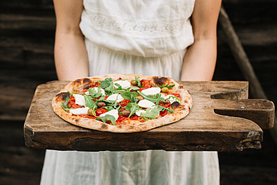 Woman holding home-made pizza on chopping board, mid section - p429m1494218 by Alberto Bogo