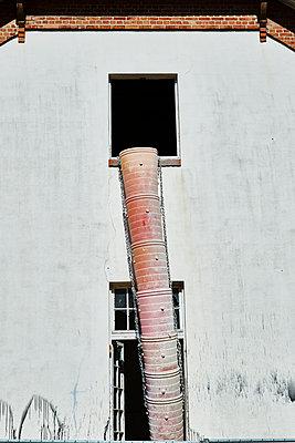 Schuttrutsche an einer Hausfassade - p851m1148581 von Lohfink