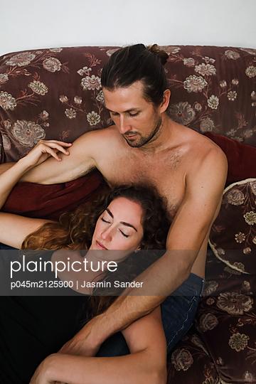 Innig zusammen auf dem Sofa liegen - p045m2125900 von Jasmin Sander