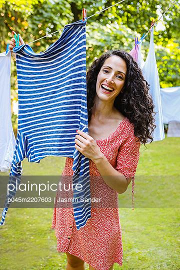 Glückliche Hausfrau die Wäsche aufhängt - p045m2207603 von Jasmin Sander
