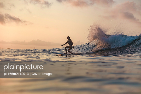 Female surfer in ocean at sunset - p1166m2112013 by Cavan Images