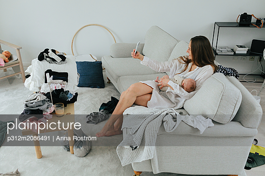 Mother with baby on sofa - p312m2086491 by Anna Roström