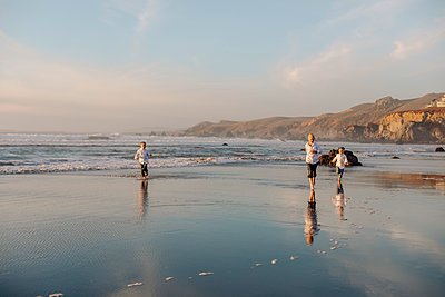 Children running during sunset in the beach - p1166m2073872 by Cavan Images