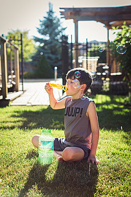 Young boy blowing bubbles in a backyard on a summer day. - p1166m2138083 by Cavan Images