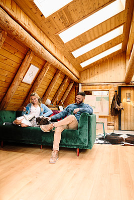 Couple with dog relaxing, reading book on cabin sofa - p1192m2093961 by Hero Images