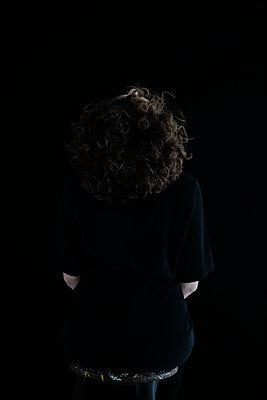 Rückansicht einer jungen Frau mit Locken die hochschaut - p1212m1127678 von harry + lidy