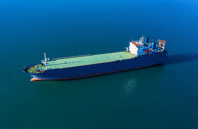 Aerial view of cargo ship in sea - p1596m2165723 by Nikola Spasov