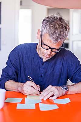 Mature man writing notepads on table  at home - p300m2030499 von Tom Chance