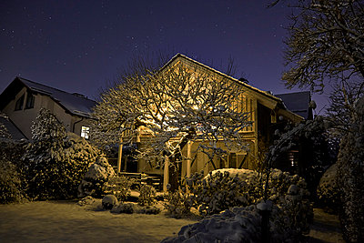 Germany, lighted one-family house with snow-covered garden in the foreground - p300m998048f by David Köhler