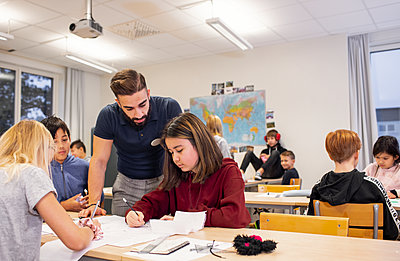Teacher helping girl in classroom - p312m2190392 by Scandinav
