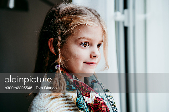 Cute girl covered in blanket looking through window while standing at home - p300m2225548 by Eva Blanco