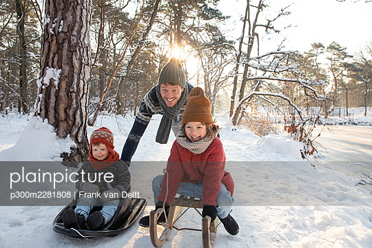 The Netherlands, Vught, father and sons playing in snowy woods - p300m2281808 von Frank van Delft