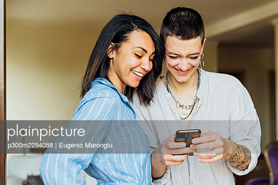 Smiling young woman using phone by girlfriend at home - p300m2294088 by Eugenio Marongiu