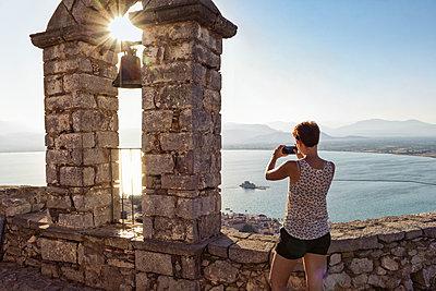 Greece, Peloponnese, Argolis, Nauplia, Argolic Gulf, woman photographing view from bell tower of Palamidi Fortress - p300m1580811 von Maria Maar