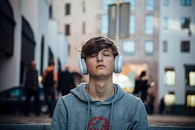 Portrait of teenager with headphones, sitting on steps in the city - p300m2166269 von Annie Hall