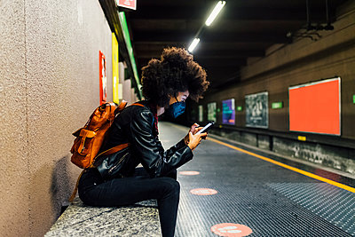 Woman with protective face mask using mobile phone while sitting at subway station - p300m2290642 by Eugenio Marongiu