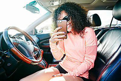 Smiling Hispanic woman in car posing for cell phone selfie - p555m1303385 by Peathegee Inc