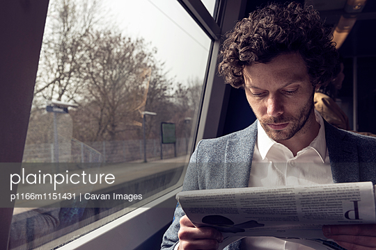 Businessman reading newspaper in train - p1166m1151431 by Cavan Images
