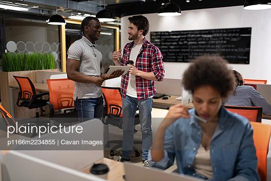 Diverse men with tablet speaking in office - p1166m2234855 by Cavan Images