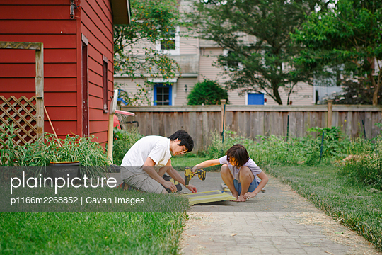 A son and father build together with electric drill in backyard - p1166m2268852 by Cavan Images