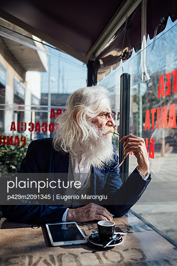 Senior businessman looking out of window in cafe, Milano, Lombardia, Italy - p429m2091345 by Eugenio Marongiu