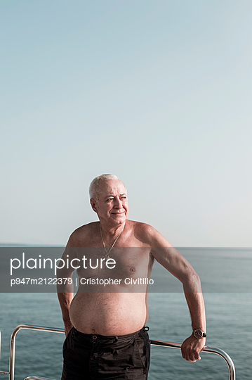 Elderly man in swimming trunks leaning against railing - p947m2122379 by Cristopher Civitillo