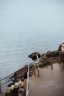 Steps leading to a flat, blurry sea in the autumn light. - p1433m1589807 by Wolf Kettler