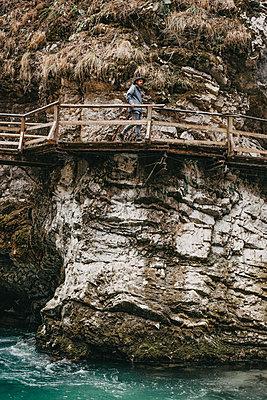 Man walking over a wooden bridge in the Vintgar Gorge in Slovenia - p1455m2081748 by Ingmar Wein