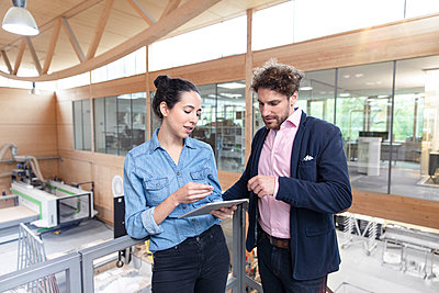 Male and female entrepreneurs discussing strategy over digital tablet near railing in factory - p300m2265969 by Florian Küttler