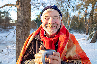 Smiling senior man in blanket holding coffee cup during winter - p300m2281856 by Frank van Delft