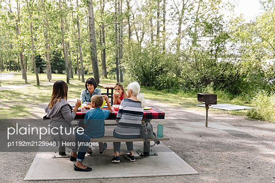 Family enjoying picnic in urban park - p1192m2129948 by Hero Images