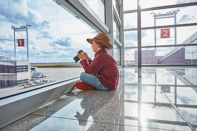 Boy sitting behind windowpane at the airport holding a camera - p300m2070854 by Stefan Schütz