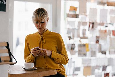 Blond businesswoman using smartphone in a coffee shop, reading text messages - p300m2103850 von Joseffson