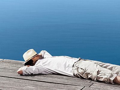 A young man lying on a jetty - p3017774f by Paul Hudson