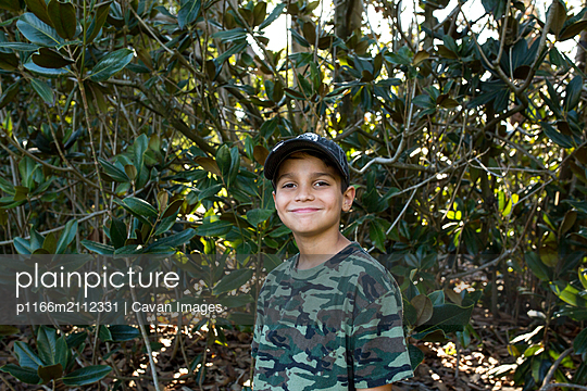 Boy smiles for a portrait outside in nature - p1166m2112331 by Cavan Images