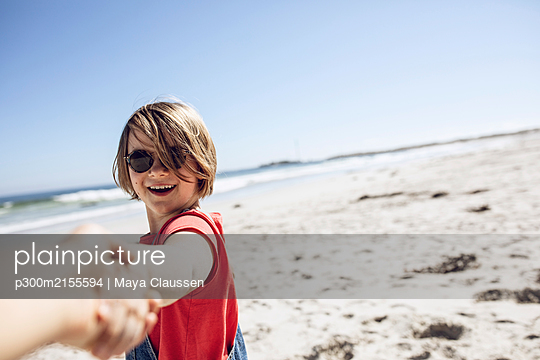Portrait of smiling girl holding hands on the beach, Cape Town, Western Cape, South Africa - p300m2155594 by Maya Claussen