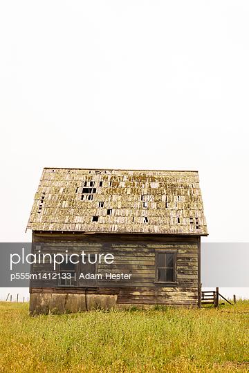 Dilapidated building in rural field - p555m1412133 by Adam Hester