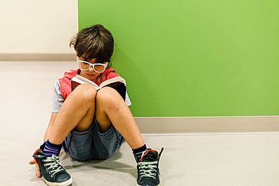 Boy with glasses reading sitting in the floor leaning against wall - p1166m2094632 by Cavan Images